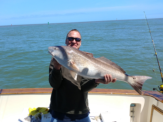 Fisherman on Amelia Island Deep Sea Fishing Charter boat proudly holding a Bull Red Fish