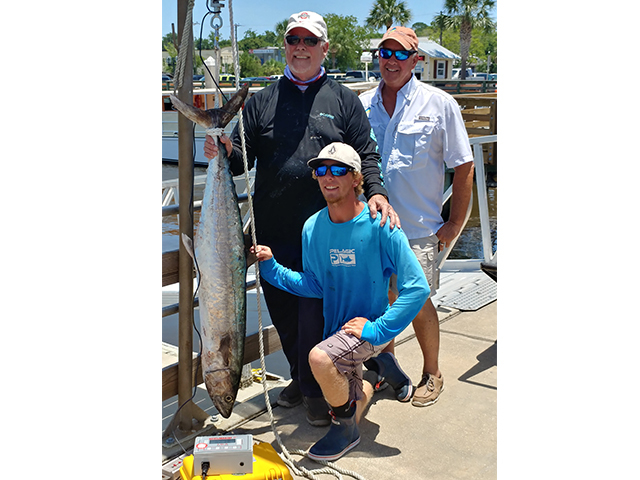 Three Fisherman on Dock Proudly Weighing their Amelia Island Deep Sea Charter Fishing Kingfish